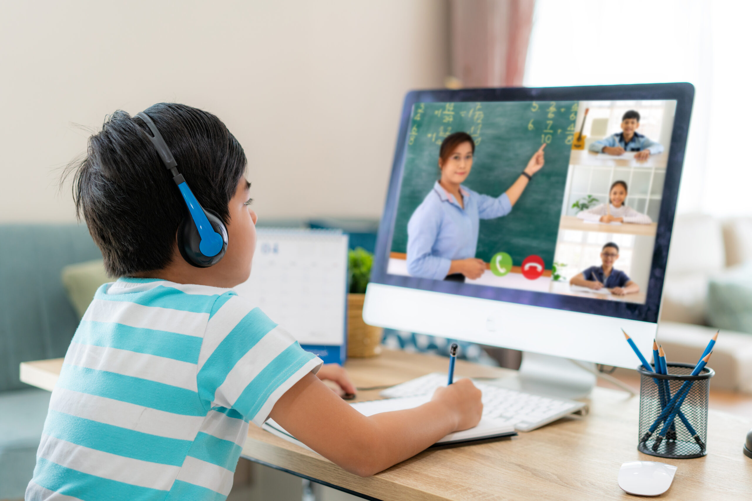 Asian boy student video conference e-learning with teacher and classmates on computer in living room at home. Homeschooling and distance learning ,online ,education and internet.